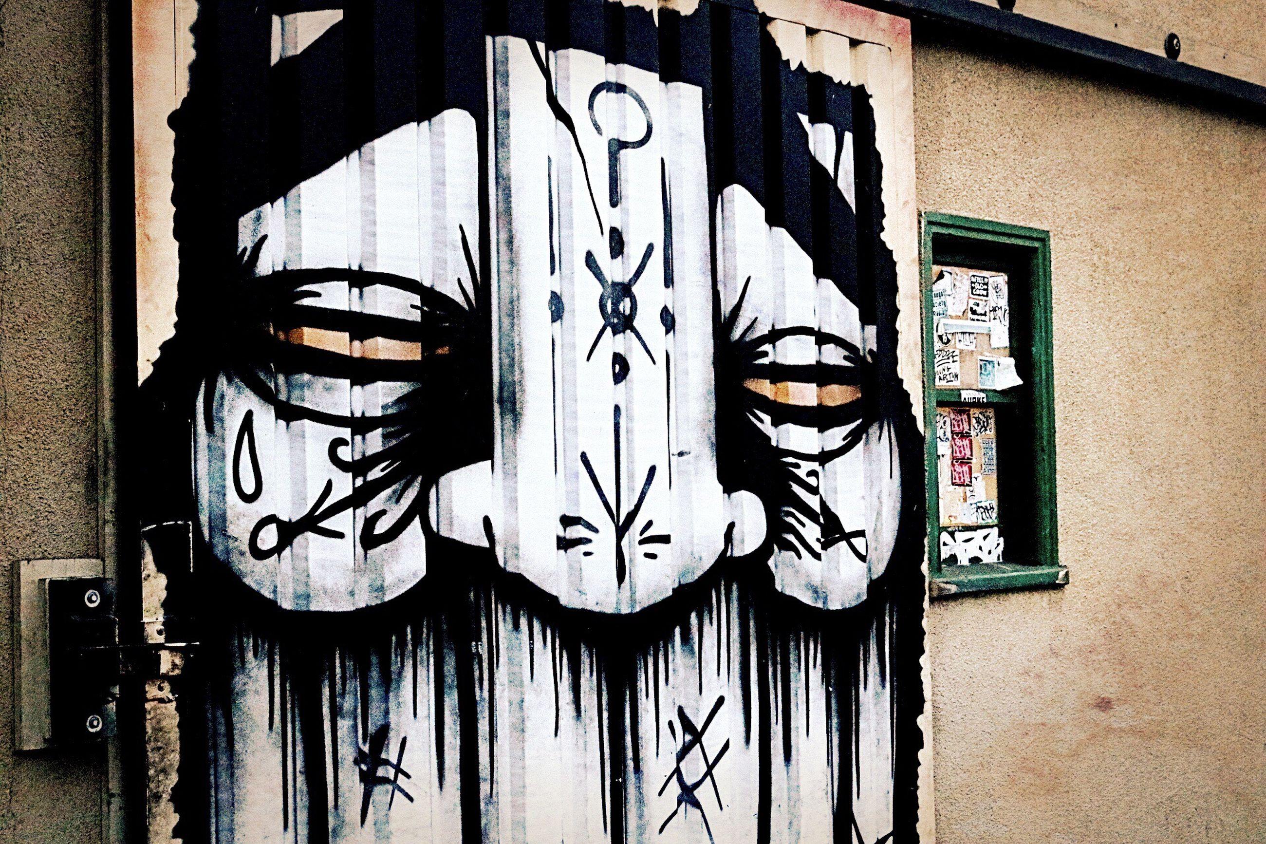 graffiti, architecture, art, built structure, wall - building feature, creativity, art and craft, building exterior, text, street art, wall, western script, human representation, communication, brick wall, outdoors, vandalism, day, mural