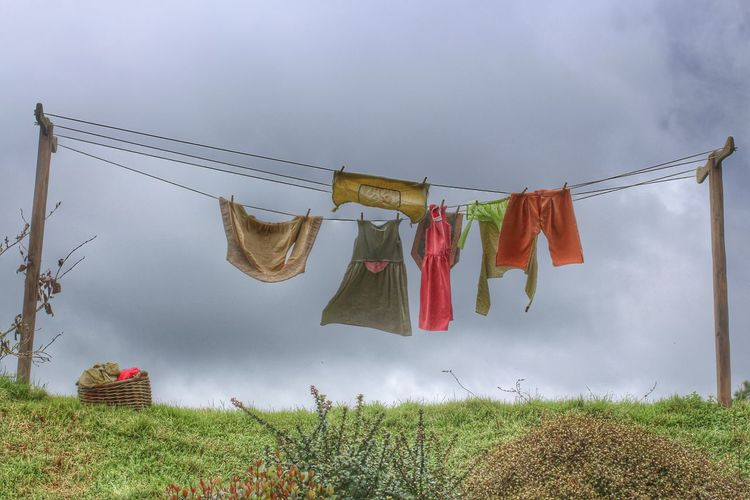 Clothes drying on clothesline over field against sky