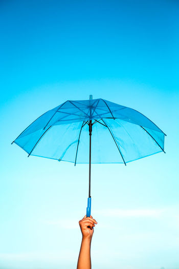 Person holding umbrella against clear blue sky