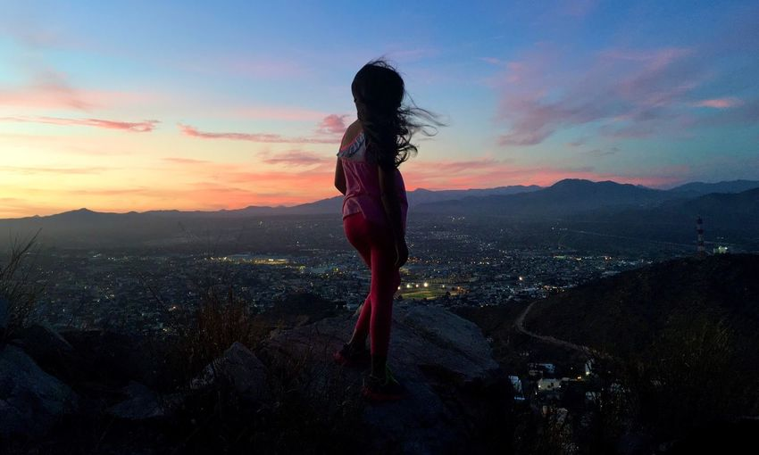 Rear view of woman standing on rock during sunset