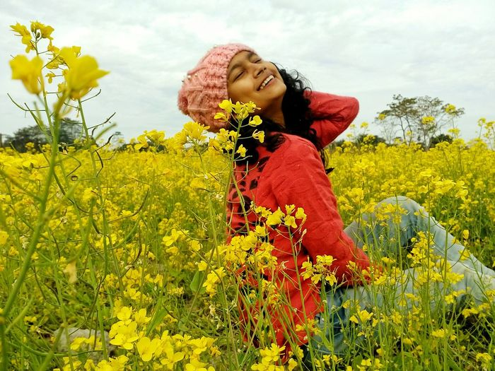 Smiling Woman Sitting Amidst Flowers On Field Against Sky