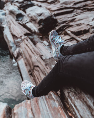 Low section of person sitting on wood