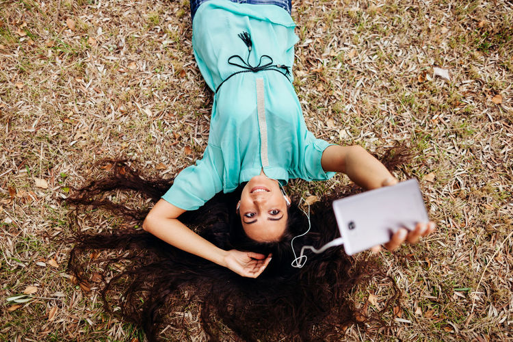 High angle portrait of woman lying down outdoors