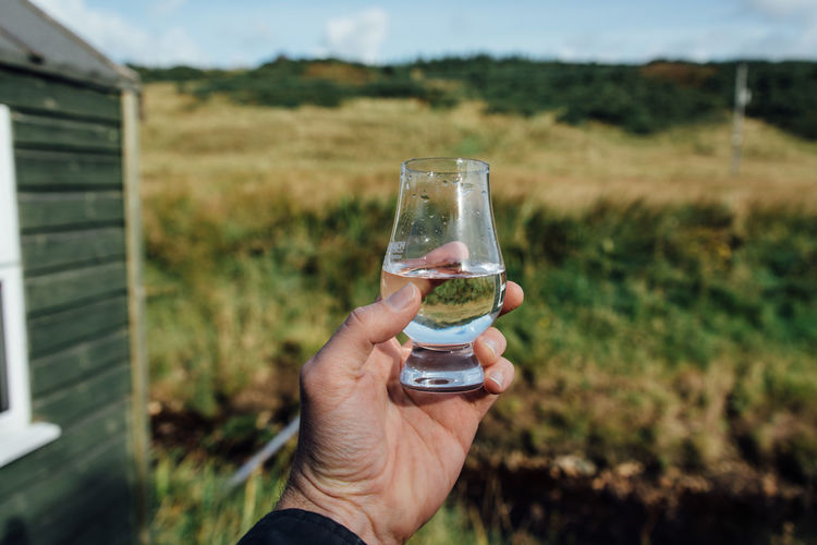 Alcohol Champagne Close-up Day Drink Drinking Glass Field Focus On Foreground Food Food And Drink Freshness Grass Holding Human Body Part Human Hand Landscape Men Nature One Person Outdoors Real People Refreshment Sky Wine Wineglass