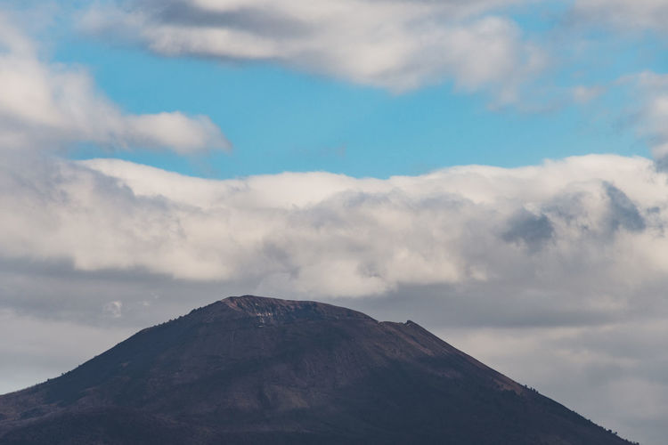 Low angle view of volcanic mountain against cloudy sky