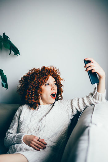 Woman taking selfie while sitting on sofa at home