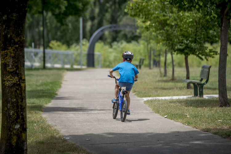 Rear view of boy riding bicycle at park