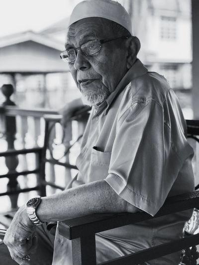 Close-up of senior man sitting on chair
