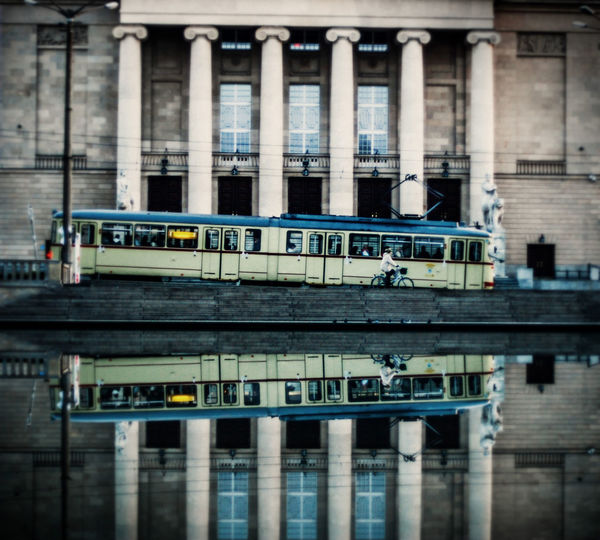 Bus moving on road by building reflecting on calm lake