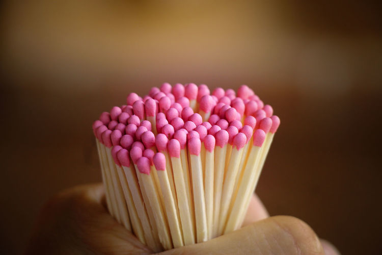 Cropped hands holding pink matchsticks