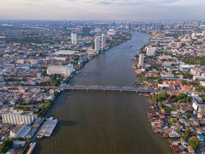 Aerial view of buildings with Chao Phraya River in transportation concept. Bangkok skyline background, Urban city in downtown area at sunset, Thailand. Financial Residential  Village Roof Houses Area Buddhism Culture Metropolitan Phraya Sunset Temple Town Landscape Skyline Modern Thai Tower Transport Energy Computer Community Background Communication Metropolis Tourism ASIA Capital Downtown Urban Architecture Business Cityscape Buildings Skyscrapers Transportation Road Street Cars Aerial Technology Smart Travel Chao Phraya Bridge Panorama Bangkok City Thailand River