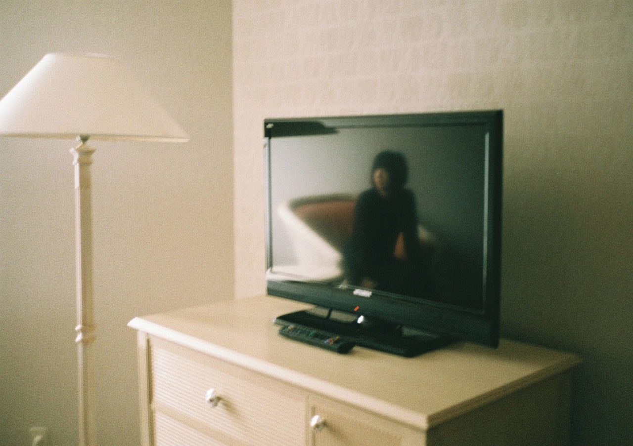 Reflection of woman on television set