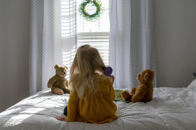 Preschool age girl sitting on bed brushing her hair in the morning sunlight Blonde Hair Home Home Life Morning Natural Light Teddy Bears Bed Bedroom Brushing Hair Child Childhood Cute Domestic Room Good Morning Hairbrush Home Interior Indoors  Kid Lifestyles Little Girl Morning Routine Real People Sitting
