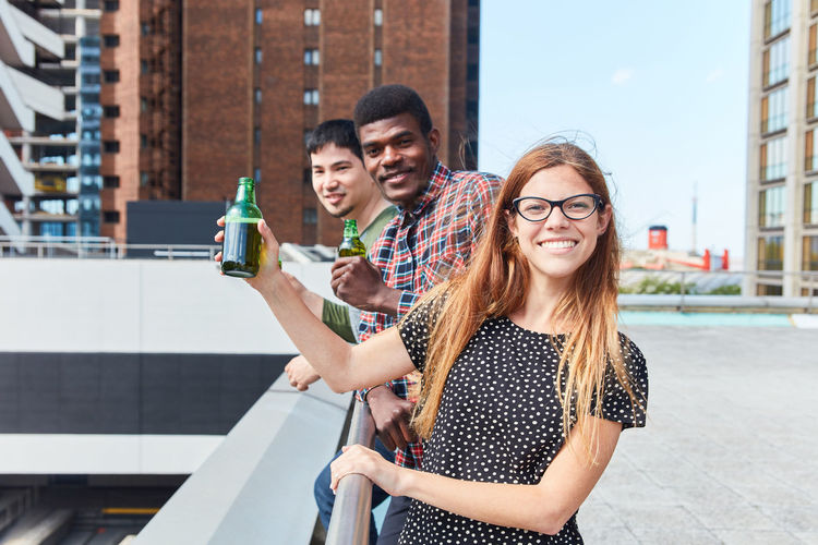 Friends holding bottles while standing on terrace in city