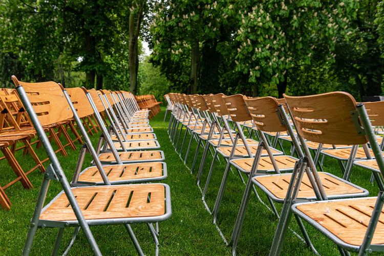 Wooden chairs stand outside in the park. empty auditorium, green grass, trees, water drops.