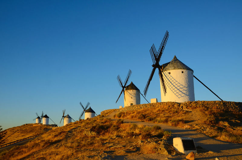 The windmills of Consuegra, featured in Cervantes novel Don Quixote, are a lovely attraction to visit in the La Mancha region in central Spain. These machines used the wind to grind grain Windmill Consuegra SPAIN Travel Architecture Landmark Landscape Old Tourism Mill Nature Outdoor Toledo Wind Building Sky Blue Traditional Spanish Hill Quijote Mancha Sunset Summer White Nobody Europe Windmills History Clouds Symbol Culture Rural Hilltop Icon Row Cervantes Don Famous Medieval Province Quixote Tourist Castilla Traditional Windmill