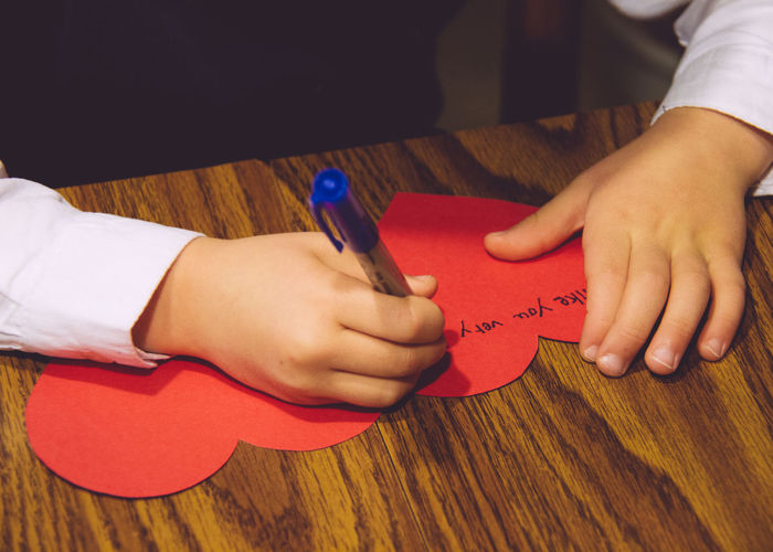 Cropped image of child writing on heart shape greeting card on table
