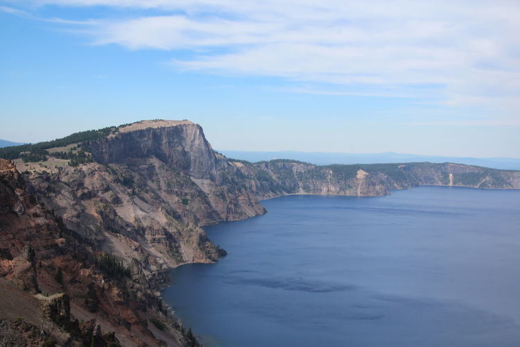 Scenic View Of Crater Lake By Cliff Against Sky