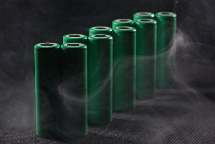 Close-up of green batteries amidst smoke on table