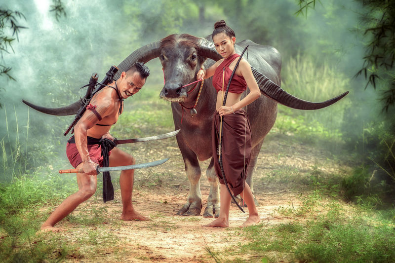 Full Length Portrait Of Warriors Standing With Buffalo In Forest