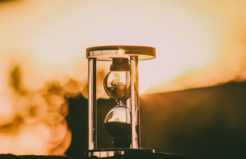 Close-Up Of Hourglass Against Sky During Sunset