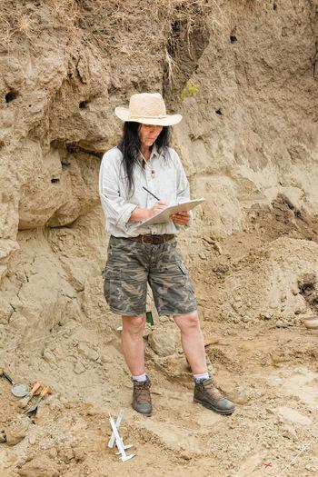 Full length of paleontologist making report