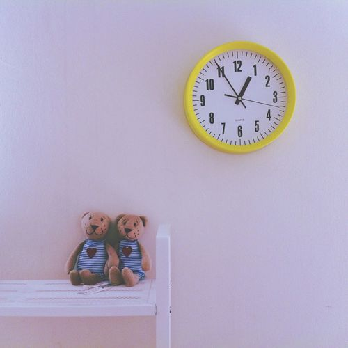 Stuffed bear toys on bench against pink wall with clock