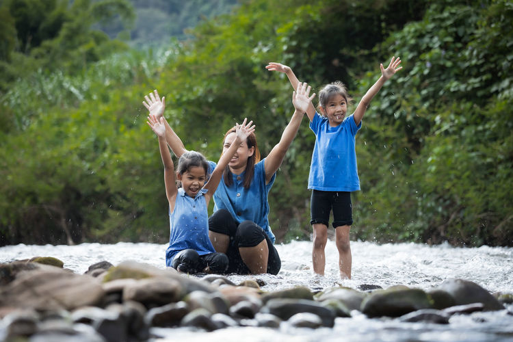 Cheerful mother with with daughter playing in river