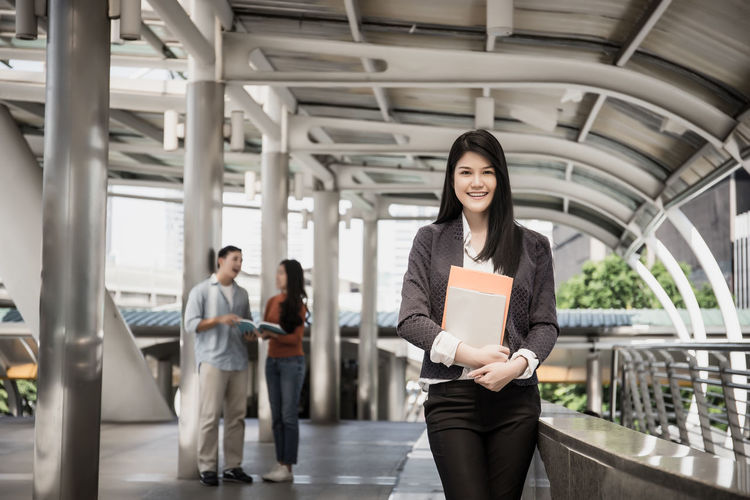 Portrait Of Woman Holding Book While Standing By Railing