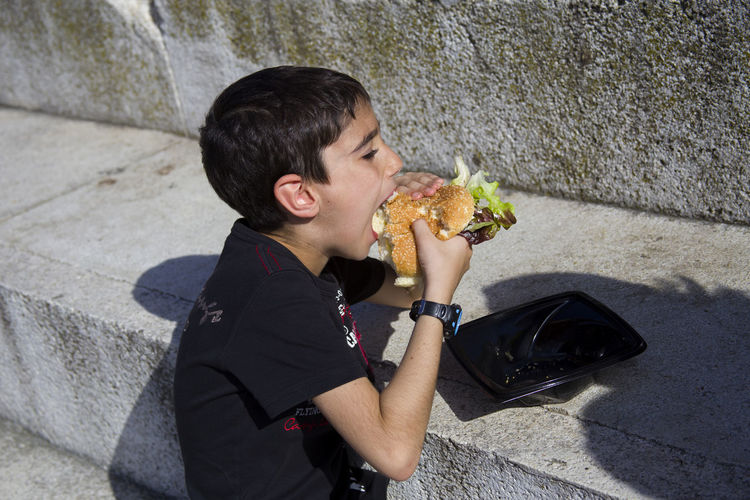 High Angle View Of Eating Burger By Wall