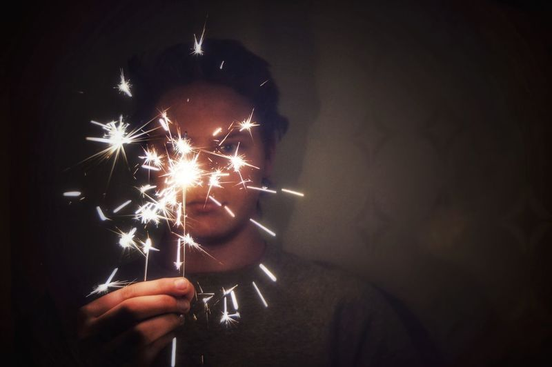 Close-Up Of Teenage Boy Holding Sparkler At Night