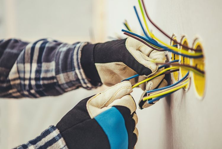 Close-up of man working on cables on wall