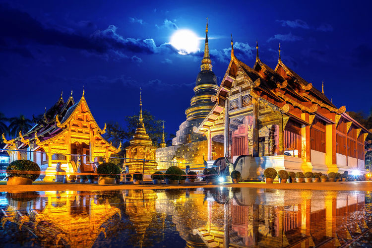 Wat Phra Singh temple at night in Chiang Mai, Thailand. Architecture Built Structure Religion Building Exterior Sky Belief Reflection Illuminated Travel Destinations Place Of Worship Spirituality Building Nature Night Cloud - Sky Water Dusk No People Outdoors Spire  Ornate