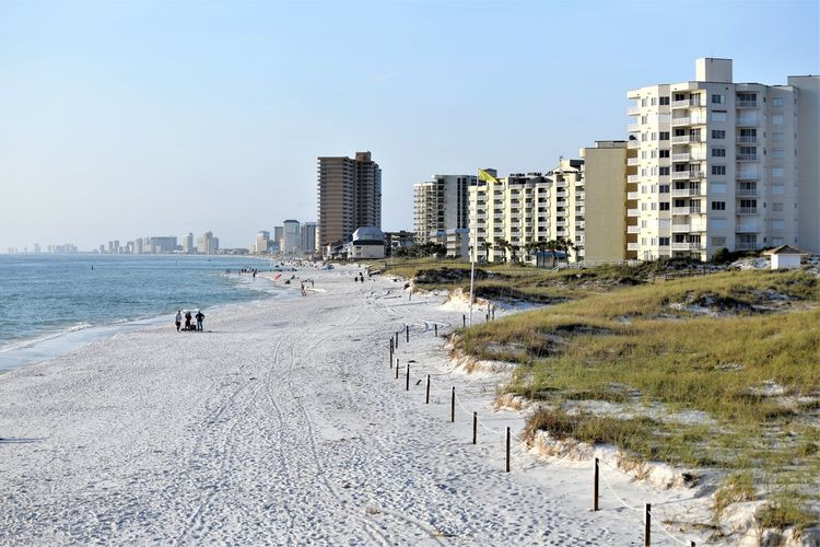Panoramic view of beach and buildings against clear sky