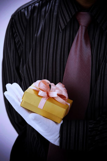 Midsection of man holding gift box