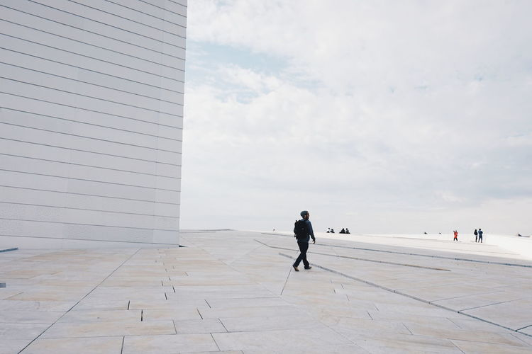 Man Walking On Walkway At Oslo Opera House Against Sky