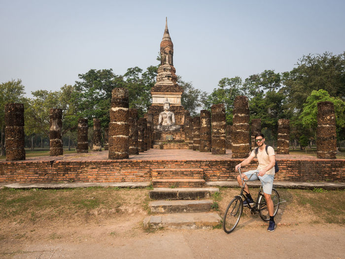 Young man riding bicycle in front of ruins of sukhothai historical park, thailand