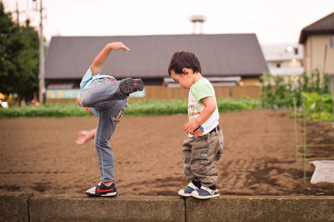 childhood, boys, full length, casual clothing, child, playing, elementary age, outdoors, two people, day, real people, leisure activity, togetherness, building exterior, people