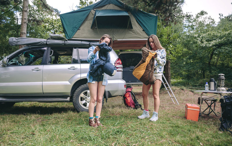 Young women opening sleeping bags in campsite with their vehicle in the background Camping Campsite Grass Hiking Horizontal Nature Travel Trip Woman Adventure Backpack Car Caucasian Equipment Female Forest Mountain Off Road Opening Outdoors Sleeping Bag Tent Two People Vehicle Young Adult