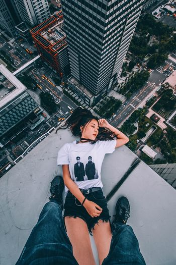 High angle view of woman using mobile phone while sitting in city