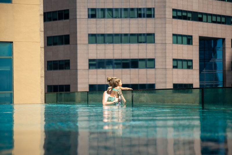 Full length of woman on swimming pool against building