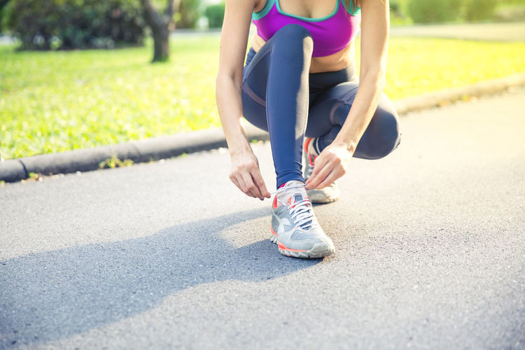 Sport background, woman is tied on shoe, ready for running in Morning light. Exercise Lifestyle Marathon Ready Ready To Go Run Day Exercising Fitness Health Healthy Lifestyle Human Leg Jogging Lifestyles Nature Outdoor Performance Road Shoe Sport Sports Sports Clothing Sunlight Warm Up Women
