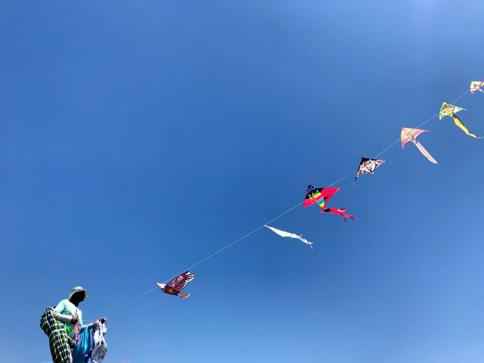 Low angle view of man flying kite against blue sky