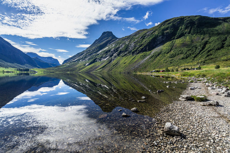 Mountain and sky reflected in Eidsvatnet lake near Geirangerfjord in a bright summer day, Sunnmore, More og Romsdal, Norway Norway Norway🇳🇴 Norwegen Scandinavia Geirangerfjord Geiranger Geiranger Fjord Geirangerfjorden Northern Europe Mountain Sky Cloud - Sky Scenics - Nature Water Tranquil Scene Beauty In Nature Tranquility Mountain Range Lake Reflection Nature Day Idyllic Non-urban Scene No People Landscape Environment Remote Outdoors Mountain Peak