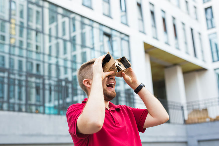 Man wearing virtual reality headset while standing outdoors