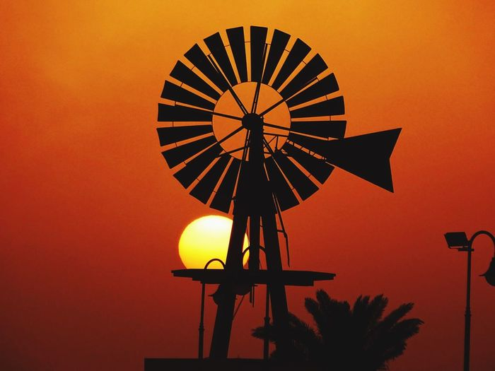 Silhouette traditional windmill against clear orange sky