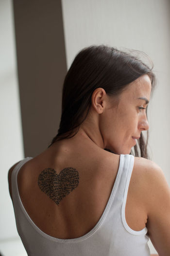 Rear view of woman with tattoo standing at home
