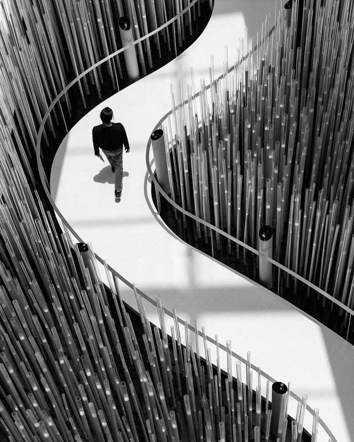 HIGH ANGLE VIEW OF MAN MOVING ON STAIRCASE IN CITY