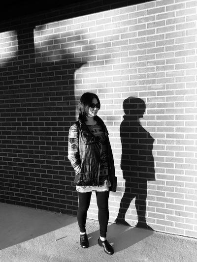 Full length of woman standing against on sidewalk against brick wall