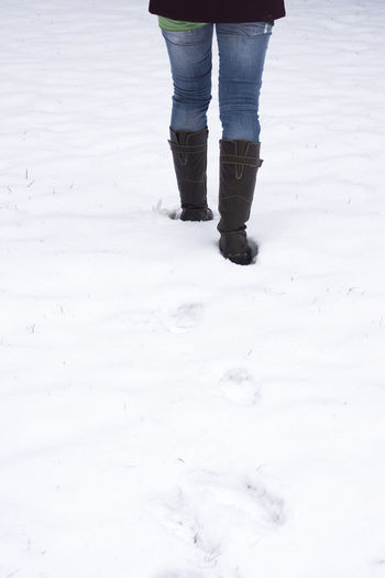 Low Section Of Woman Walking In Snow